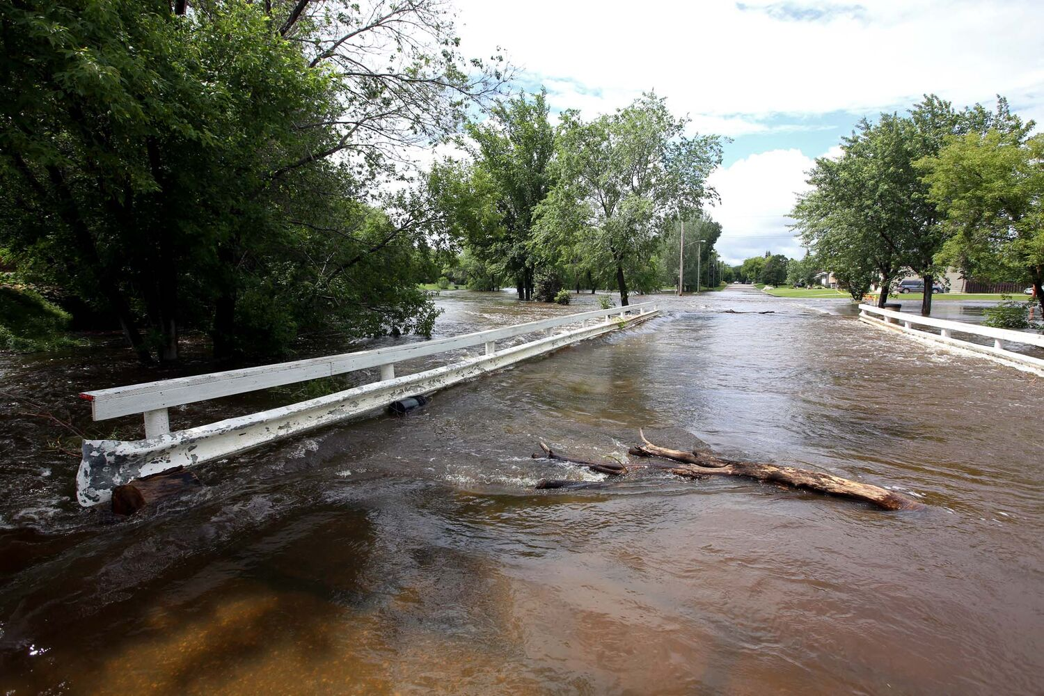 The swollen Gopher Creek in the town of Virden flows over a bridge on Monday.  (Tim Smith / Brandon Sun)