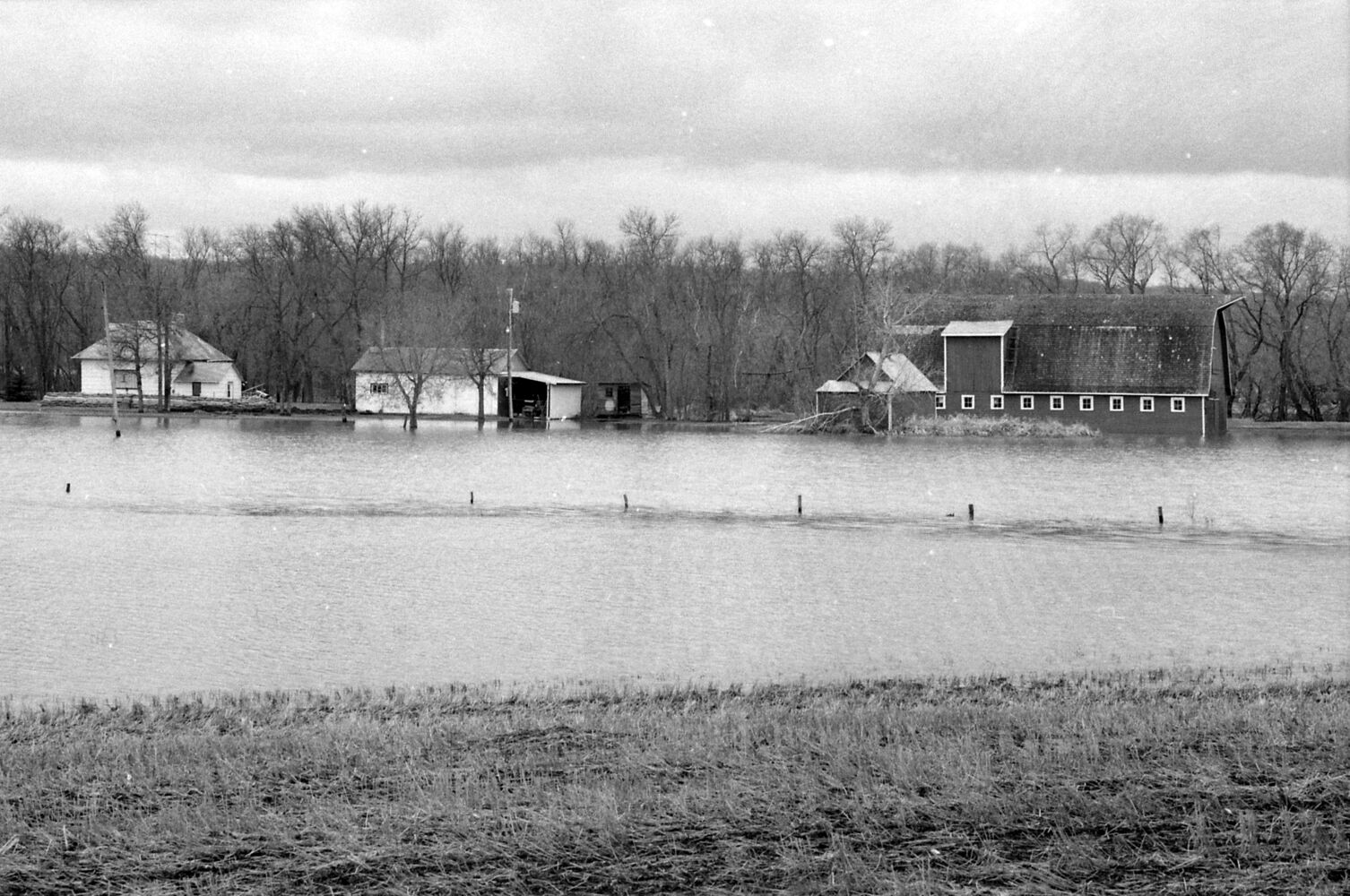 """A barn sits partially submerged, although the house, at left, is protected by sandbags. The precise location isn't certain; the image is from a roll of photos identified only as """"Kenton Lenore"""" from April 27, 1995. (Dirk Aberson / Brandon Sun archives)"""