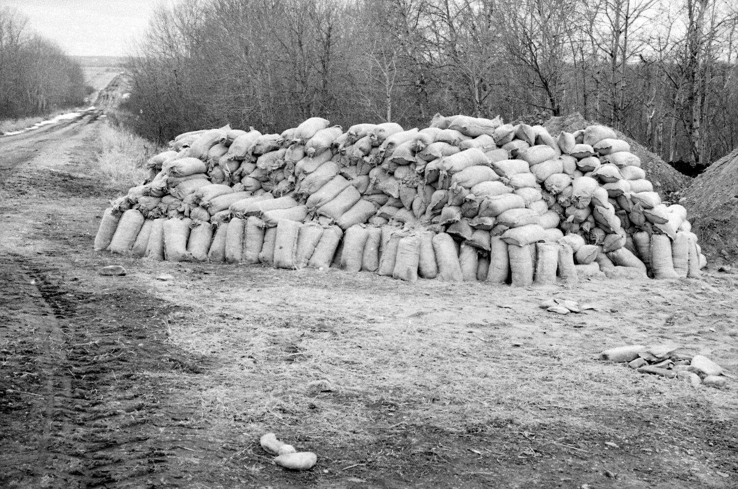 """A sandbag stockpile sits ready for use along a rural Manitoba road. The precise location isn't certain; the image is from a roll of photos identified only as """"Kenton Lenore"""" from April 27, 1995. (Dirk Aberson / Brandon Sun archives)"""