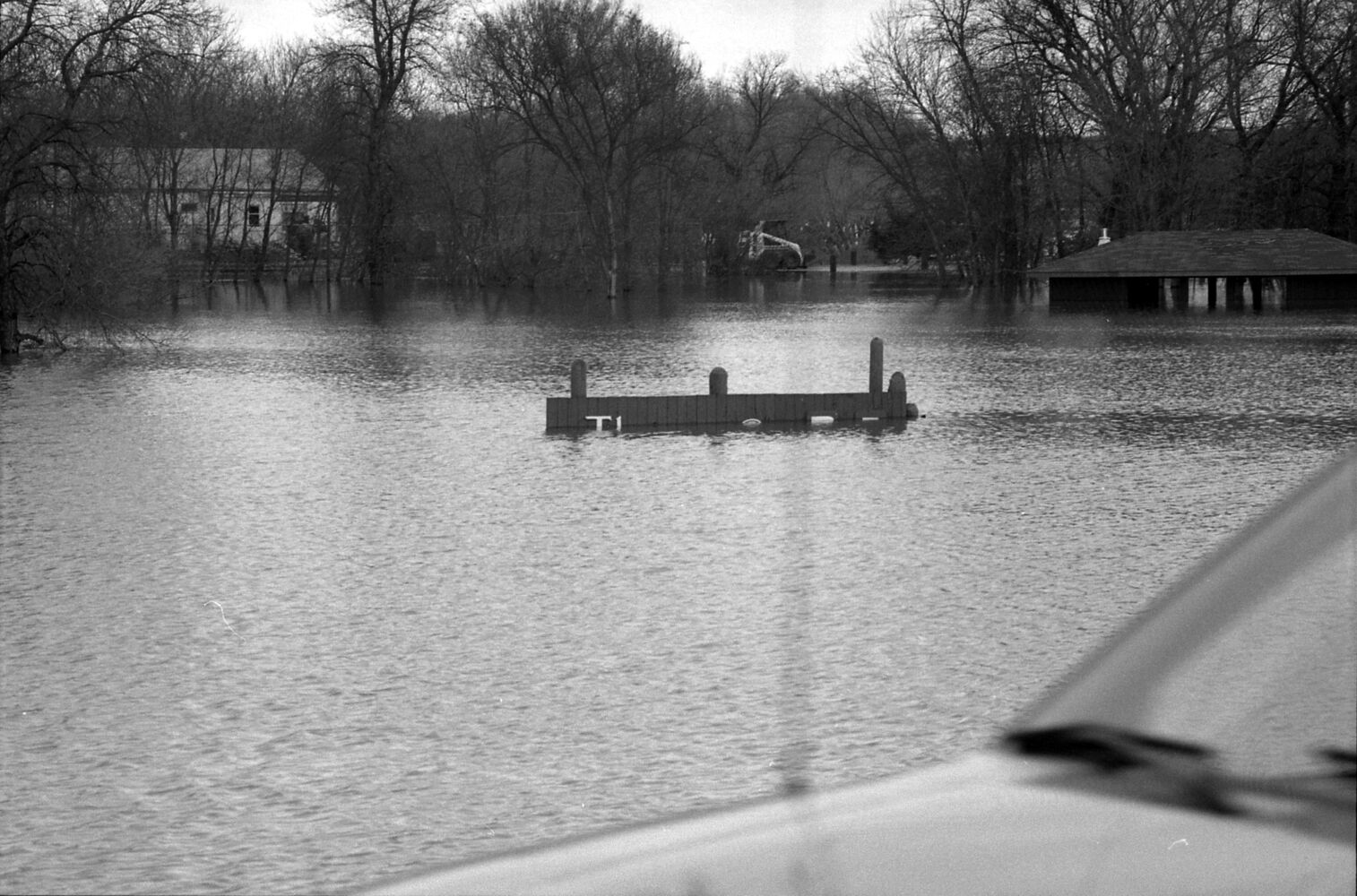 Flooding nearly covers the top of the sign marking Eleanor Kidd Park during the 1995 Assiniboine River flood. The sandbagged building that at that time housed the Brandon Humane Society is seen through the trees at left. (Drik Aberson / Brandon Sun archives, April 25, 1995.)