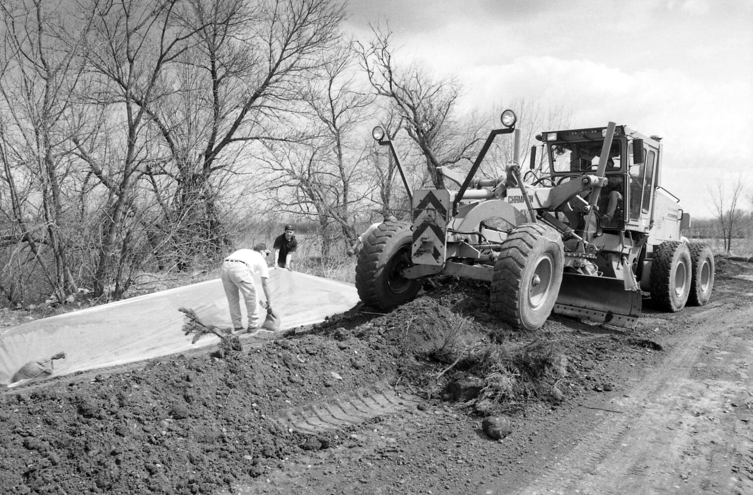 A grader and sandbaggers work on the roads during the 1995 flood fight. (Dirk Aberson/ Brandon Sun archives, April 24, 1995)