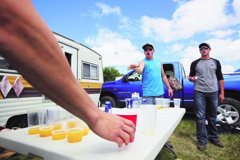 Colt Meloney throws a ping-pong ball while playing the drinking game beer pong with Ryley Dayholos (R) and other friends in the campground during Dauphin's Countryfest north of Riding Mountain National Park on Thursday.