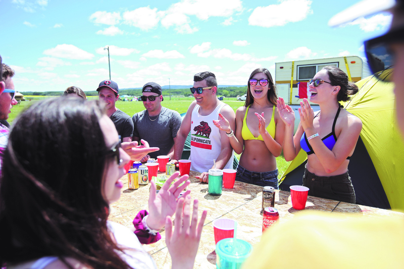 A group of friends play a drinking game called flip cup at a camp site during Dauphin's Countryfest north of Riding Mountain National Park on Thursday.