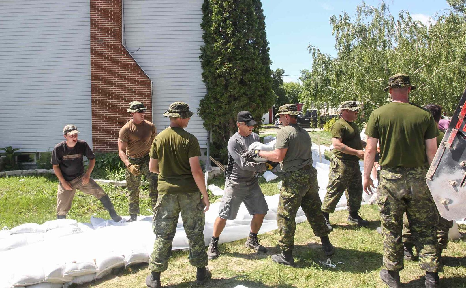 Soldiers from CFB Shilo and volunteers help fortify Kevin Van Camp's home near St. Francois Xavier Sunday afternoon.  (Mike Deal / Winnipeg Free Press)