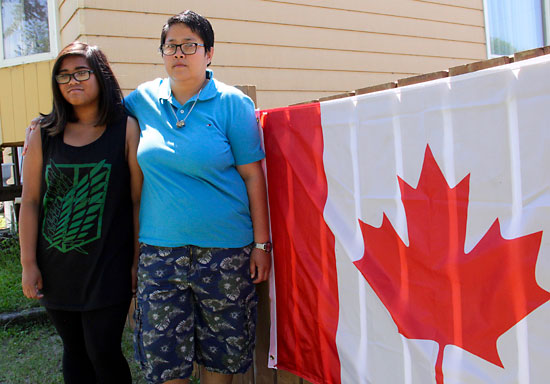 Rochelle Unico and her daughter Sofia, immigrants from the Philippines, put up a Canadian flag outside their Neepawa home. They say they were disheartened to read racist graffiti targeting Asians in their community.