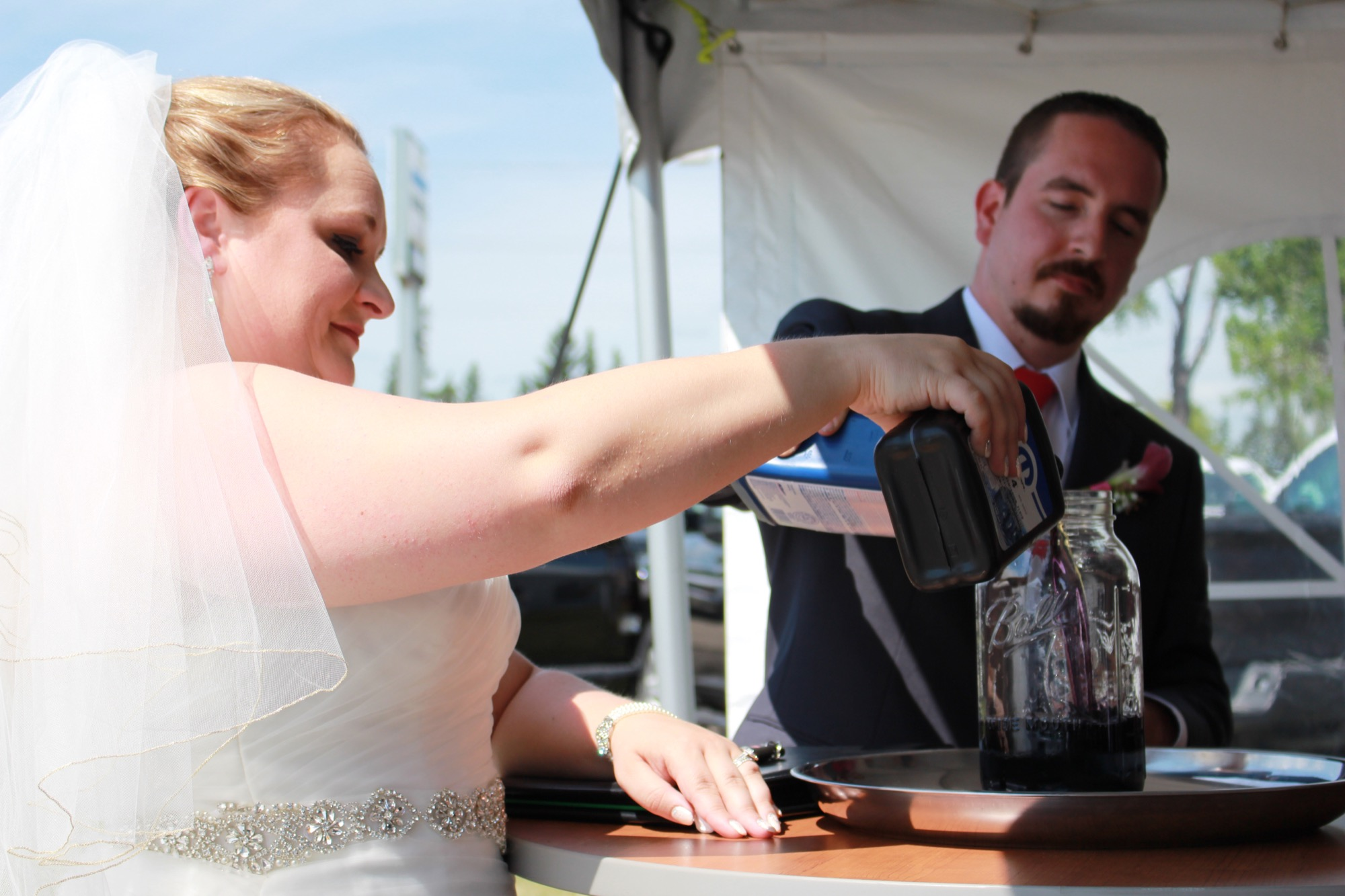 Tanya Magee and Shaun Alexander tied the knot in the parking lot between their respective car dealerships of employment — Murray Chrysler Dodge Jeep Ram Westman and Murray Chevrolet Cadillac Buick GMC Brandon — on Saturday. They ended the emotional ceremony by mixing two jugs of motor oil together into a mason jar, to symbolize their union.