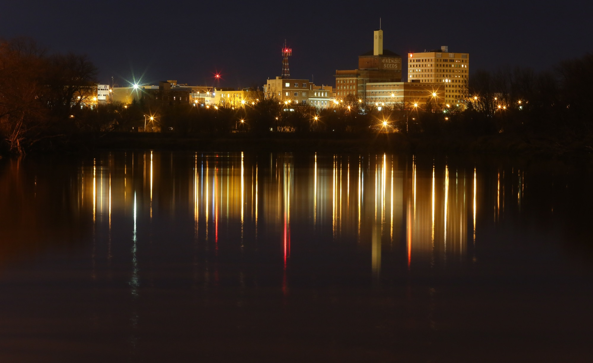 "The Brandon skyline is reflected on the Assiniboine River. KPMG's latest ""Competitive Alternatives"" report notes that Brandon has a cost index of 84.2, which is the lowest among those Canadian cities included in the report from Manitoba to the West Coast."