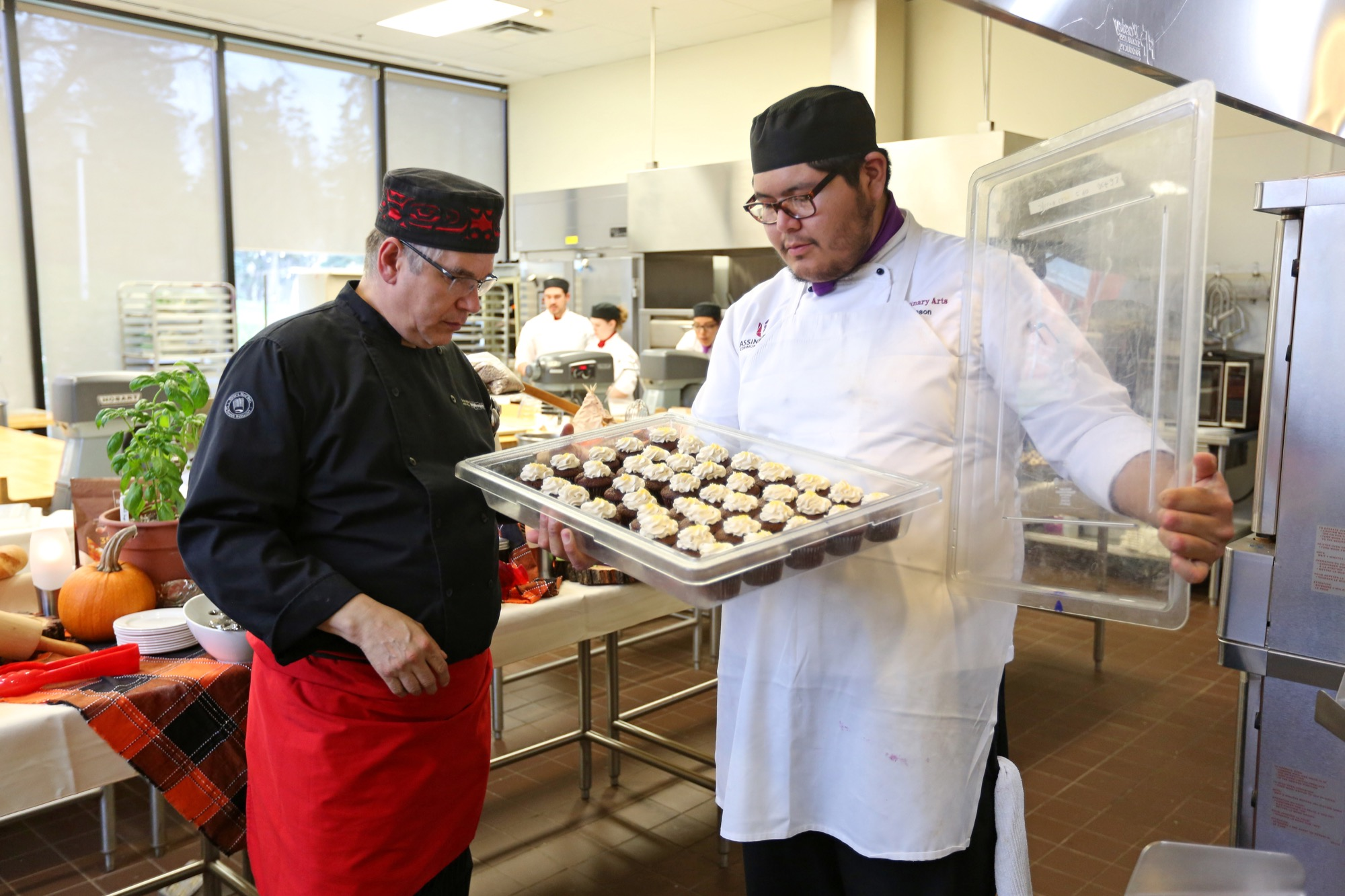 Chef David Wolfman looks over gourmet cupcakes held by Jason Huntinghawk, a second-year Manitoba Institute of Culinary Arts student at Assiniboine Community College, while teaching the MICA students Indigenous cooking skills.