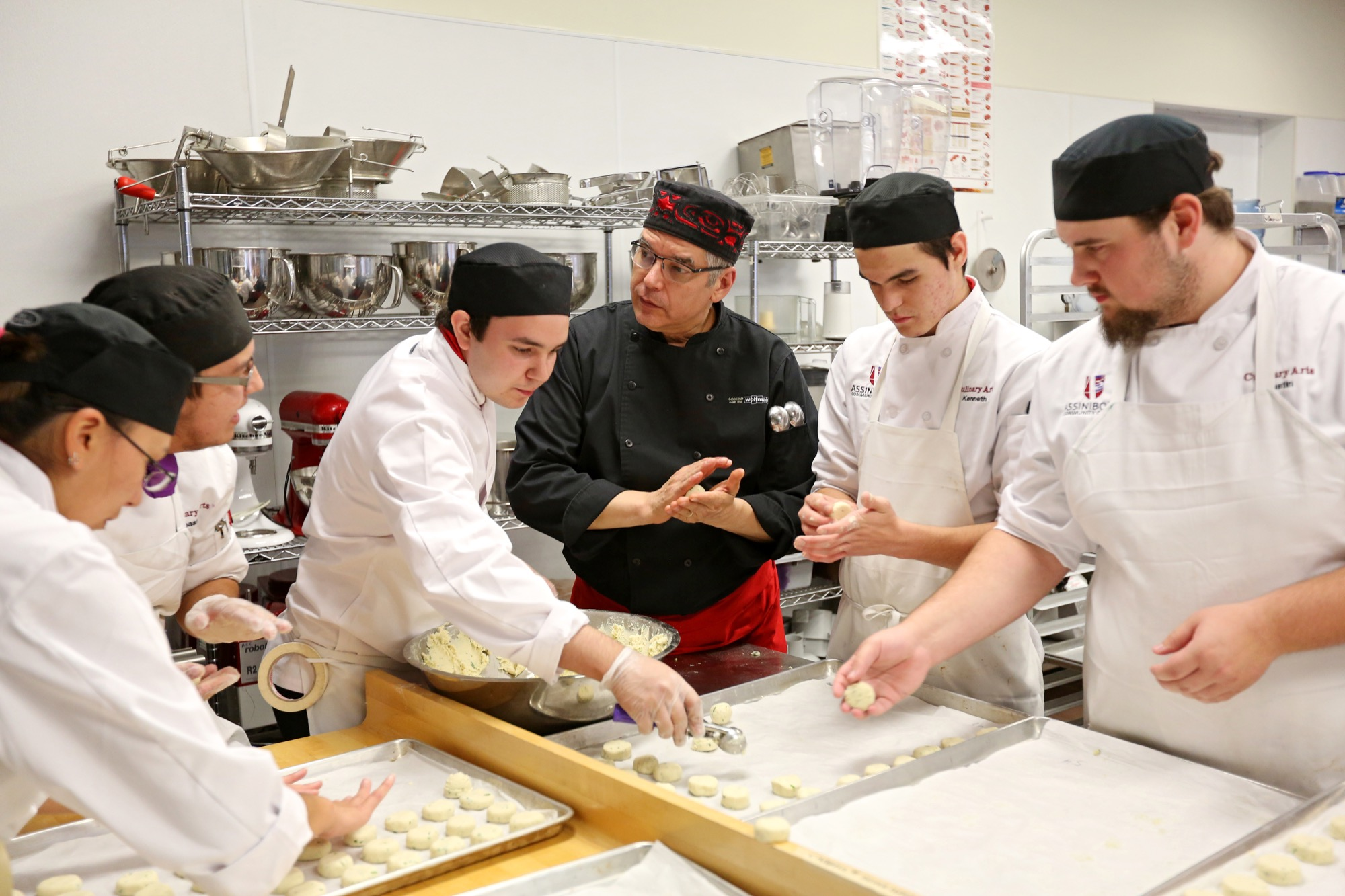 Internationally renowned chef David Wolfman works with Manitoba Institute of Culinary Arts students at Assiniboine Community College's North Hill campus on Wednesday, teaching them Indigenous cooking skills.