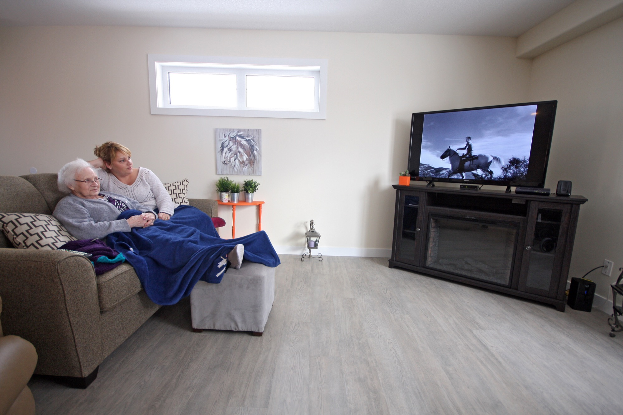 Daughter on Call seniors housing complex resident Ruth Molnar watches a black and white movie with health care aide Cori Behrman on Monday, a few days after the six-unit building opened.