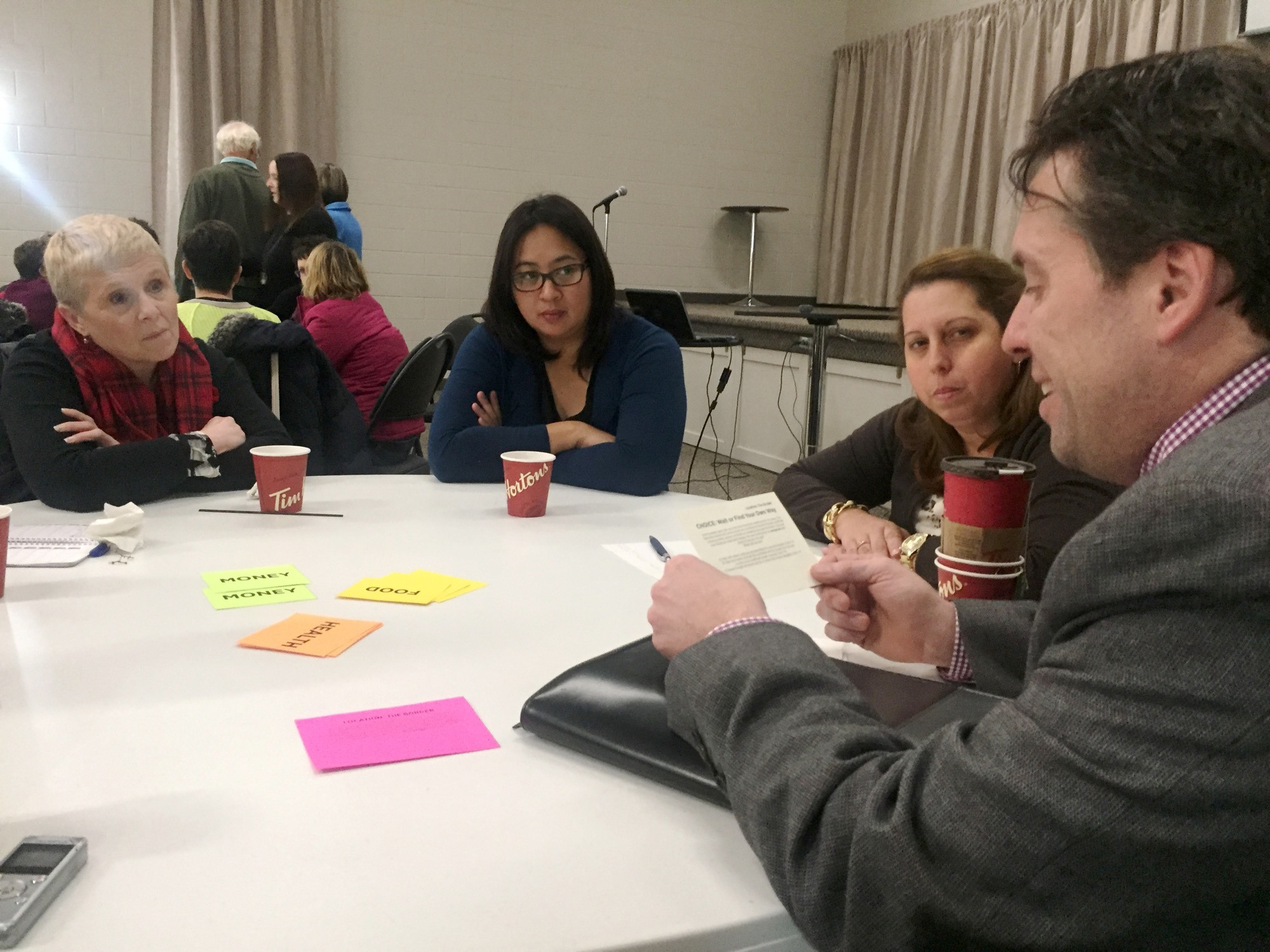 "Shawn Lehman reads options for our ""family"" to consider at a forced migration simulation with Penny McKinnon, from left, Joy Escalera and Mayumi Perez Cala."