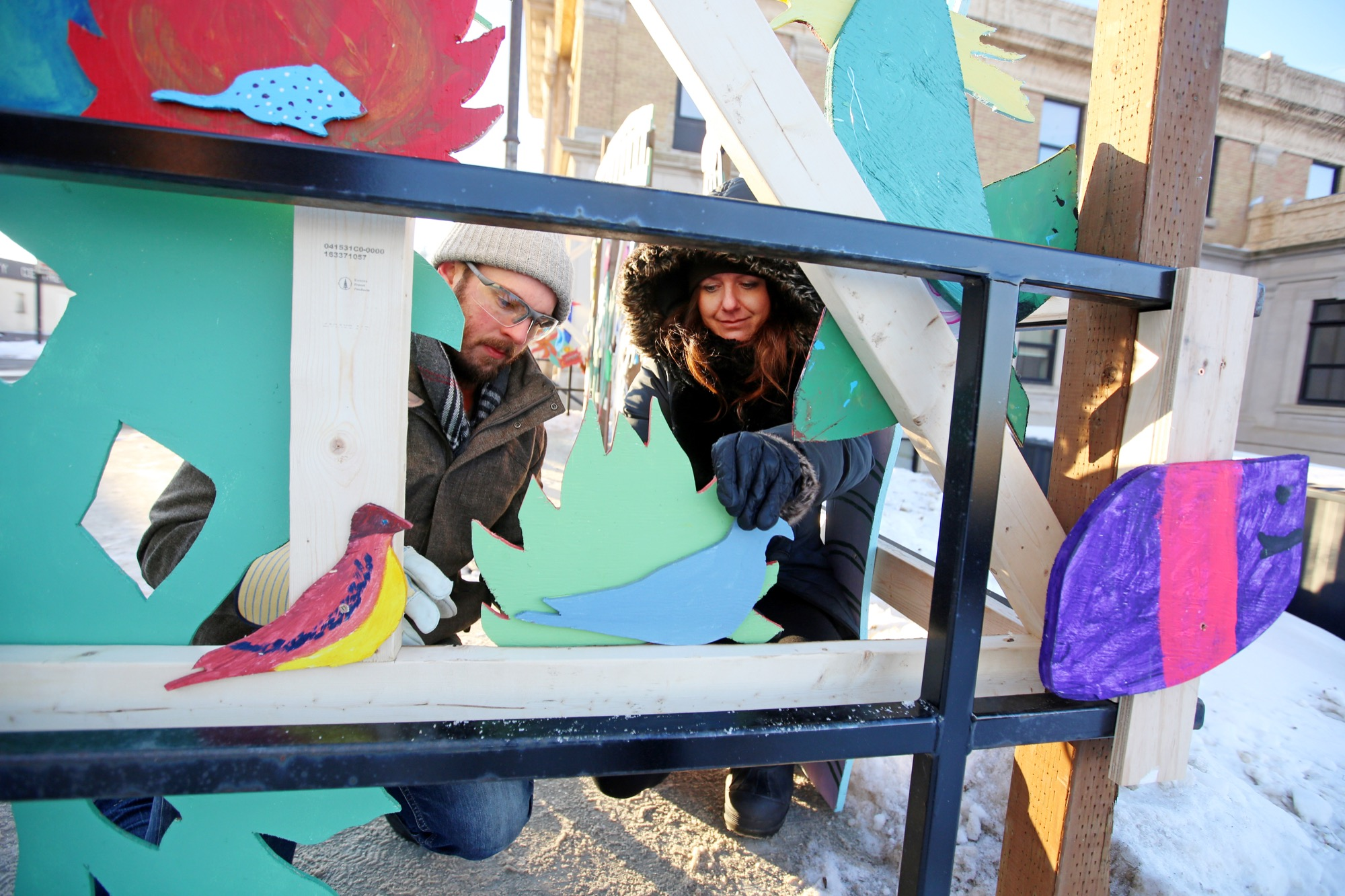 Kevin Bertram and Chris Cooper, project co-ordinator with the Winter Garden organizing committee, help install an outdoor art installation outside Westman Immigrant Services on Pacific Avenue in January.