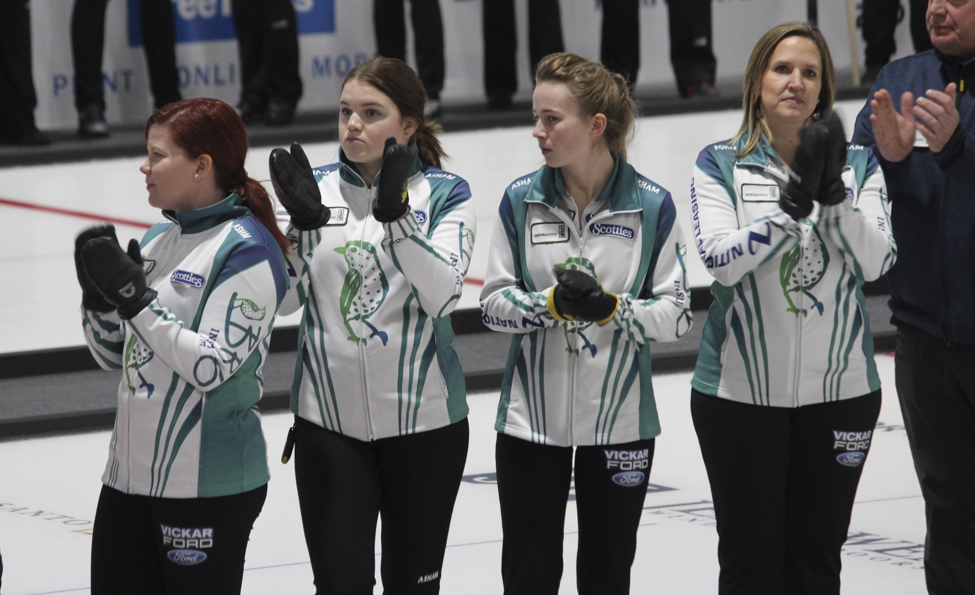 The Dauphin team of skip Lisa Hale-Menard, from left, third Meghan Walter, second Emilie Rafnson, lead Laurie Macdonell and coach Ray Baker look on/appluad during the opening ceremonies of the Manitoba Scotties Tournament of Hearts in Killarney on Wednesday evening.