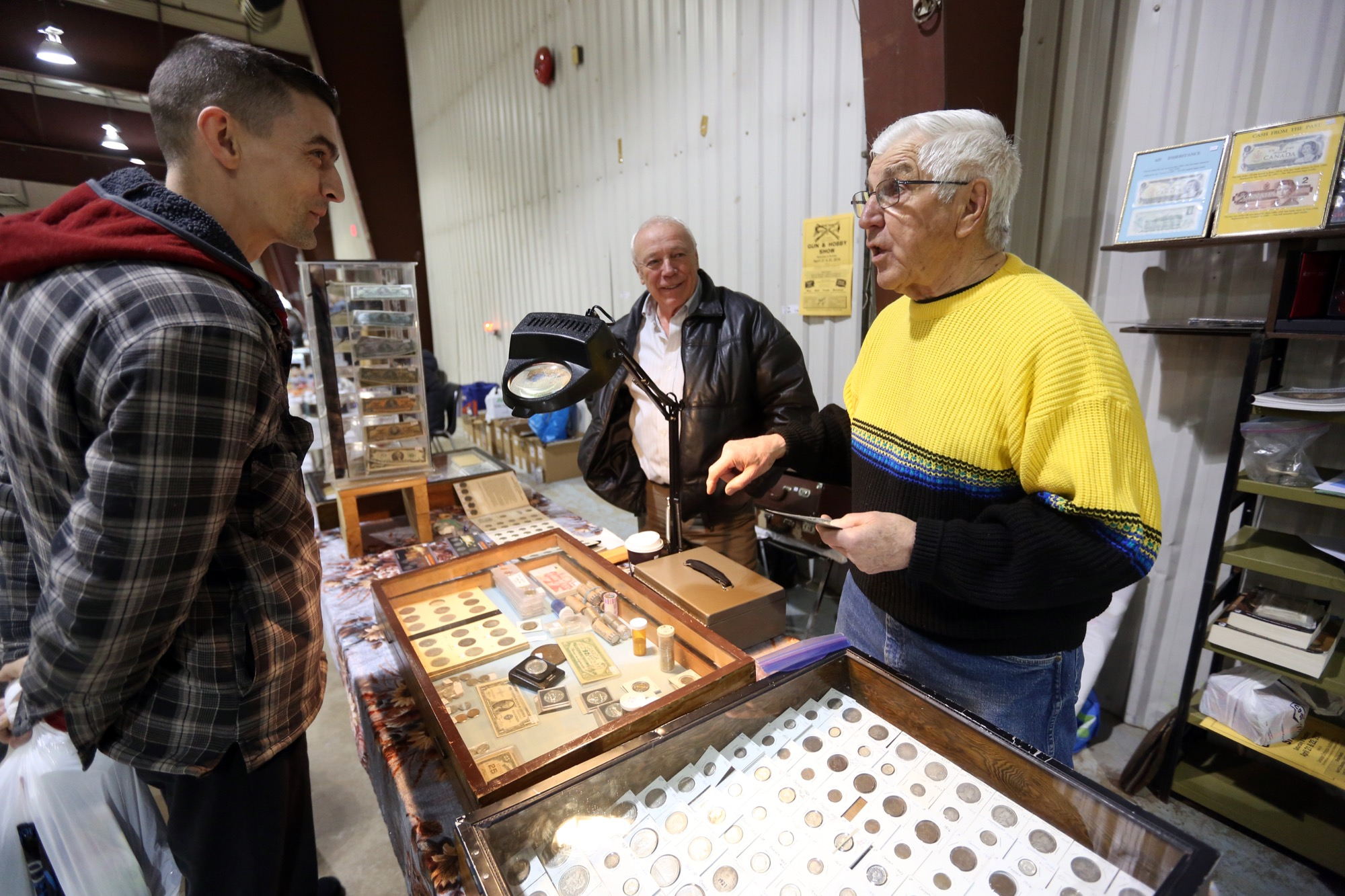 Terry Wozney, left, a private coin collector from Dauphin, chats with a fellow garage sale attendee Saturday in the Manitoba Room of the Keystone Centre.