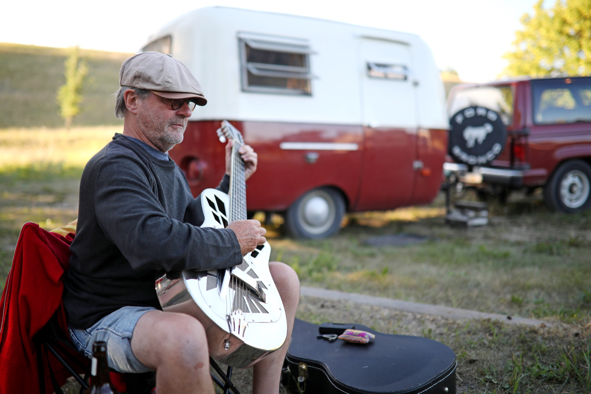 Jim Houston of Vancouver plays guitar outside his 1972 Boler camper while parked for the night at Grand Valley Campground on Tuesday evening.