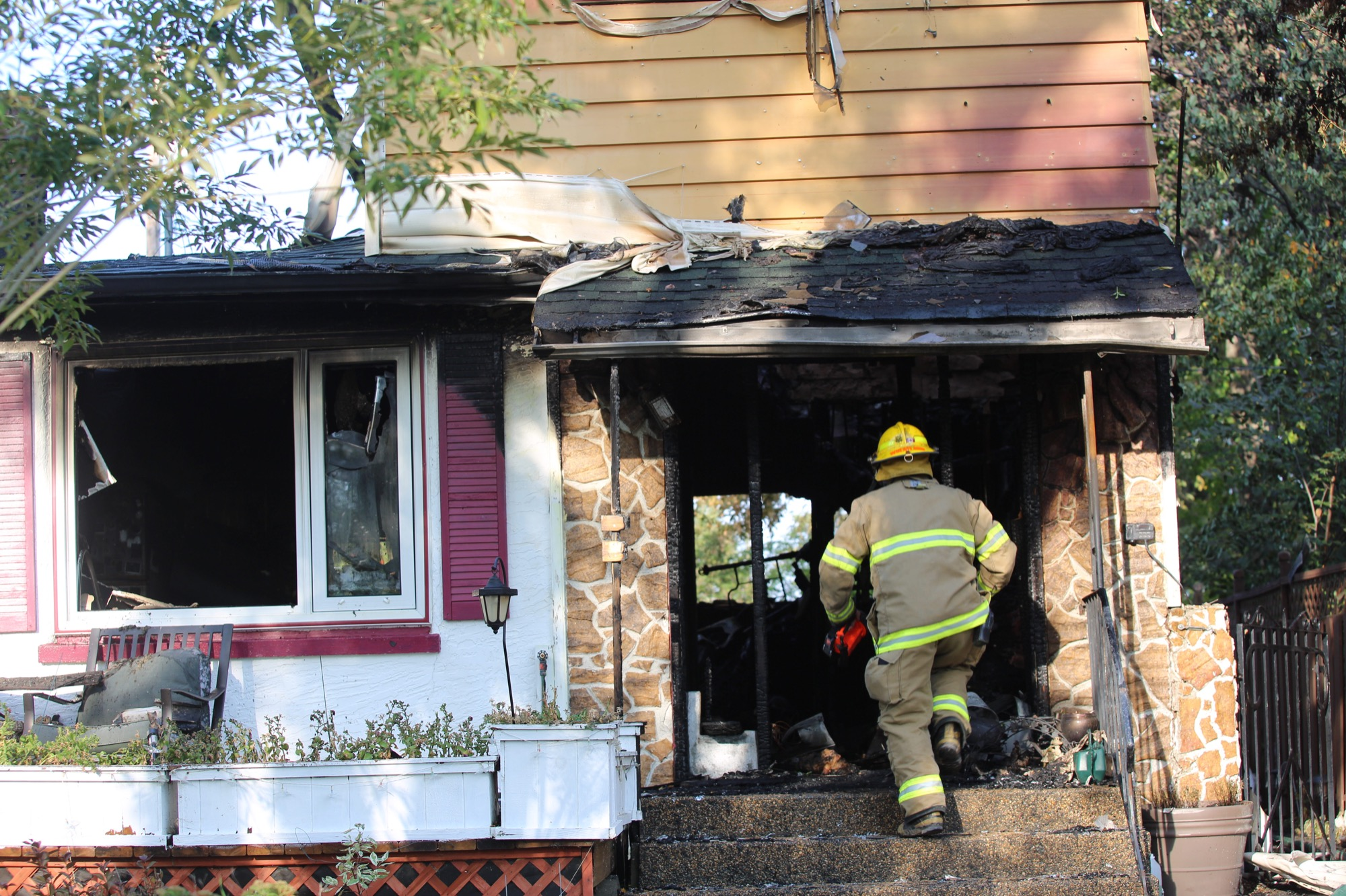 A firefighter walks back inside 842 23rd St. on Sunday morning after an early morning fire destroyed parts of the house.