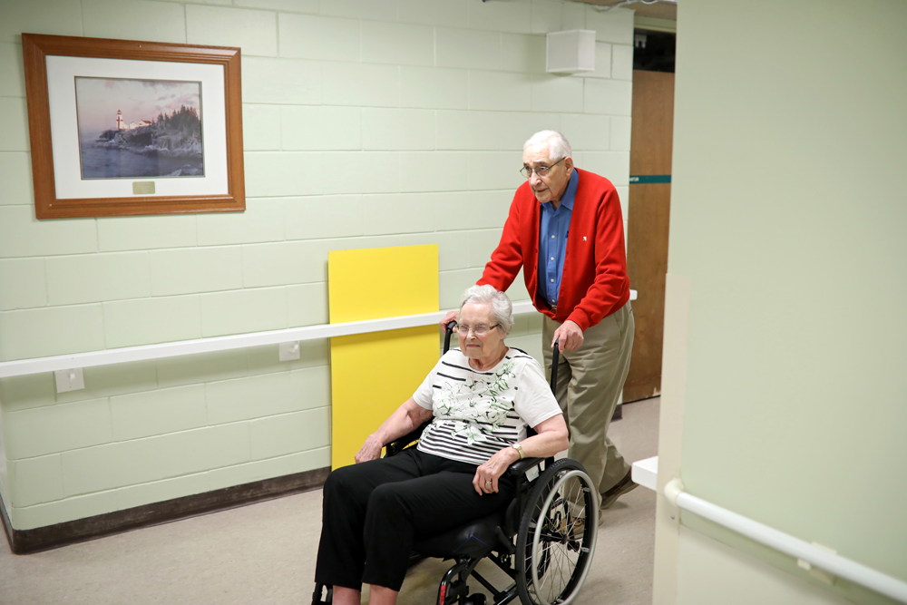03102018 Al Smith takes his wife Dorothy from her room to a common area so they can visit at Fairview Personal Care Home on 13th St. in Brandon on Tuesday afternoon. (Tim Smith/The Brandon Sun)