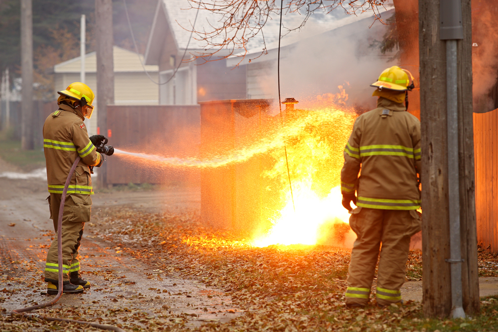 10102018 Brandon Fire and Emergency Services members pour water on a fire from a downed power line in an alley in the 1200 block of 26th Street on Wednesday. The fire ignited a garbage bin and a fence and the power to the area had to be cut before firefighters could properly douse the blaze. (Tim Smith/The Brandon Sun)