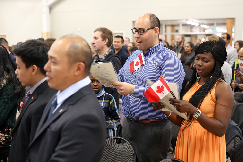 10102018 Efrain Rojas and Fatimat Idris sing the Canadian national anthem alongside fellow new Canadians during a citizenship ceremony at the Dome Building on Wednesday. 95 people from 14 different countries became Canadian citizens during the ceremony. (Tim Smith/The Brandon Sun)