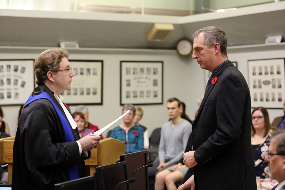 Master Robert Patterson swears in Bruce Luebke as the councillor for South Centre Thursday night at City Hall. (Michael Lee/The Brandon Sun)