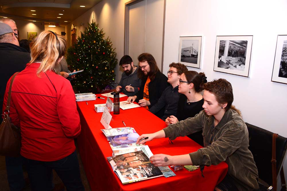 Illustrators (from right) Grace Buitenhuis, Merissa Mayhew, Jeremy Carter, Dakota Bicklmeier and Tim Brown autograph comic books they created to raise money for the Art Gallery of Southwestern Manitoba's arts program during a fundraiser Saturday at the gallery.