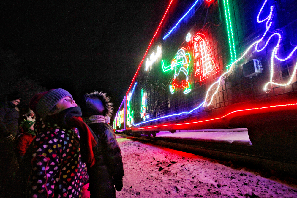 Kids look up at the colourful lights of the Canadian Pacific Holiday Train as it arrives in Brandon on Tuesday night. (Matt Goerzen/The Brandon Sun)