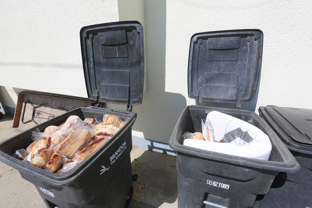 Unopened bags of bread products are pictured discarded in garbage bins behind Bible Baptist Church on Fourth Street on Monday. (Colin Slark/The Brandon Sun)