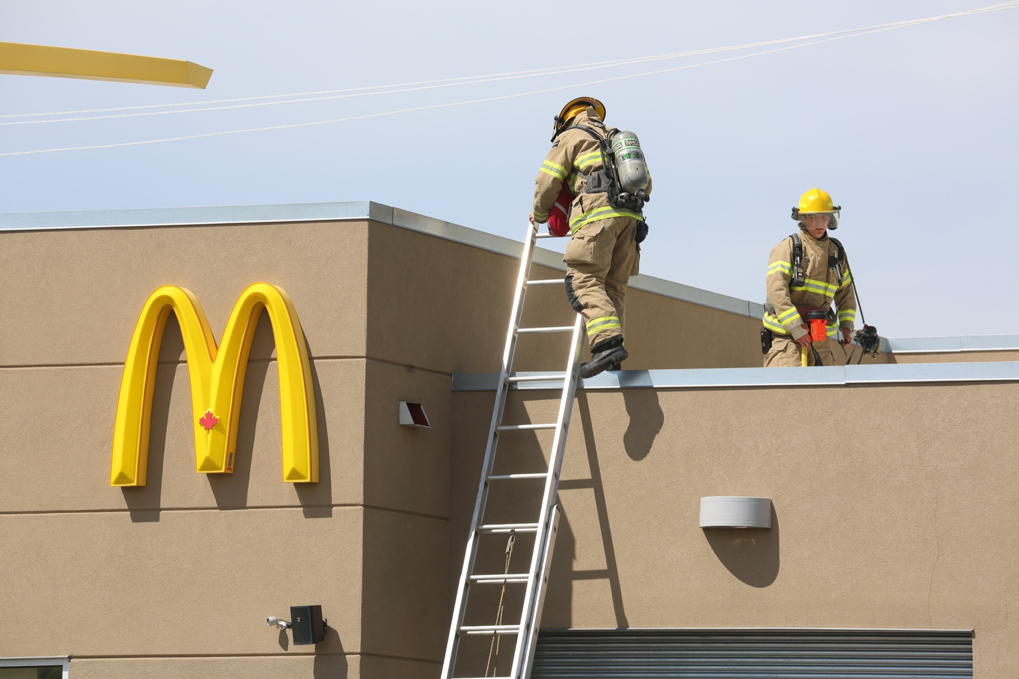 FIrefighters inspect the roof of the McDonald's location at 2626 Victoria Avenue after a kitchen fire. A spokesperson from McDonald's said that no one was hurt and that the damage was not excessive.