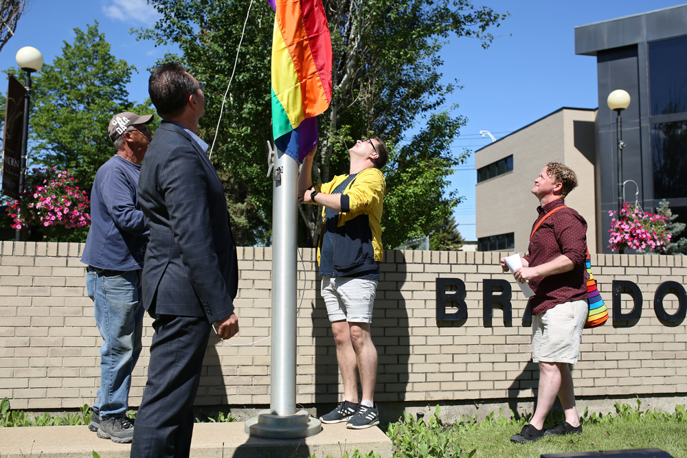 Brandon Mayor Rick Chrest (second from left) and Kenneth Jackson (right), watch as Brandon Pride 2019 chairperson Stefon Irvine, raises the Pride flag at Brandon City Hall on Monday to kick off Brandon's 10th Annual Pride Week. (Tim Smith/The Brandon Sun)