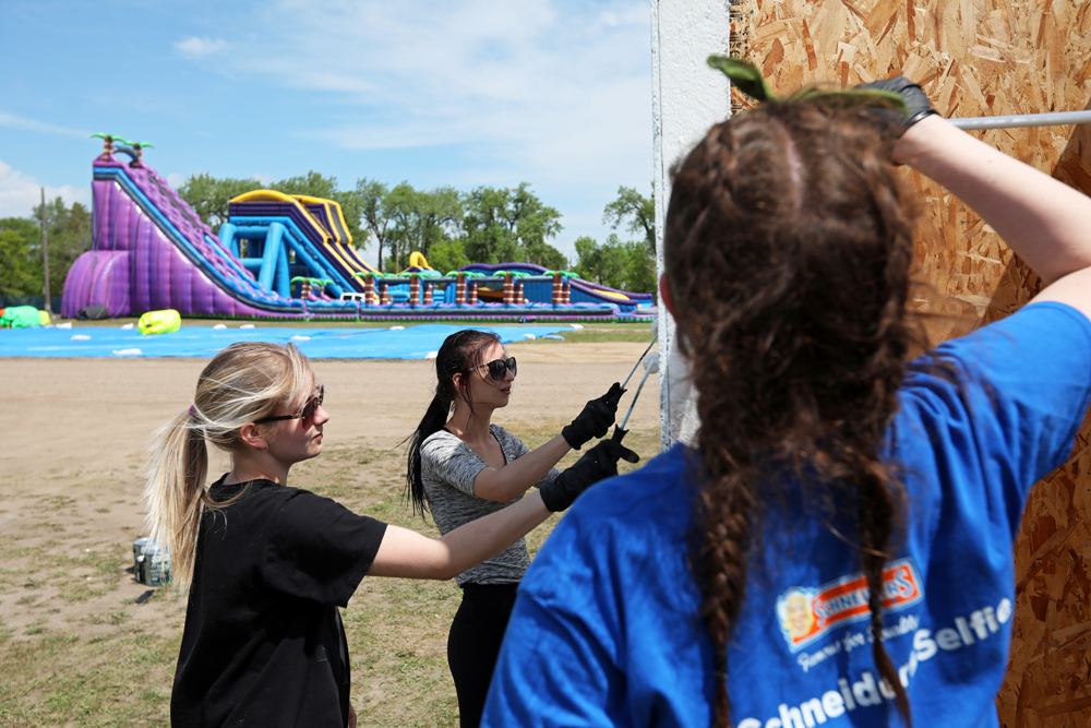 Oceanna Michel, Marisa Berkshire and Emily Hull paint a set of change rooms during set-up for the Brandon Bouncy Castles summertime water park at the Keystone Centre grounds on Tuesday afternoon.  (Tim Smith/The Brandon Sun)