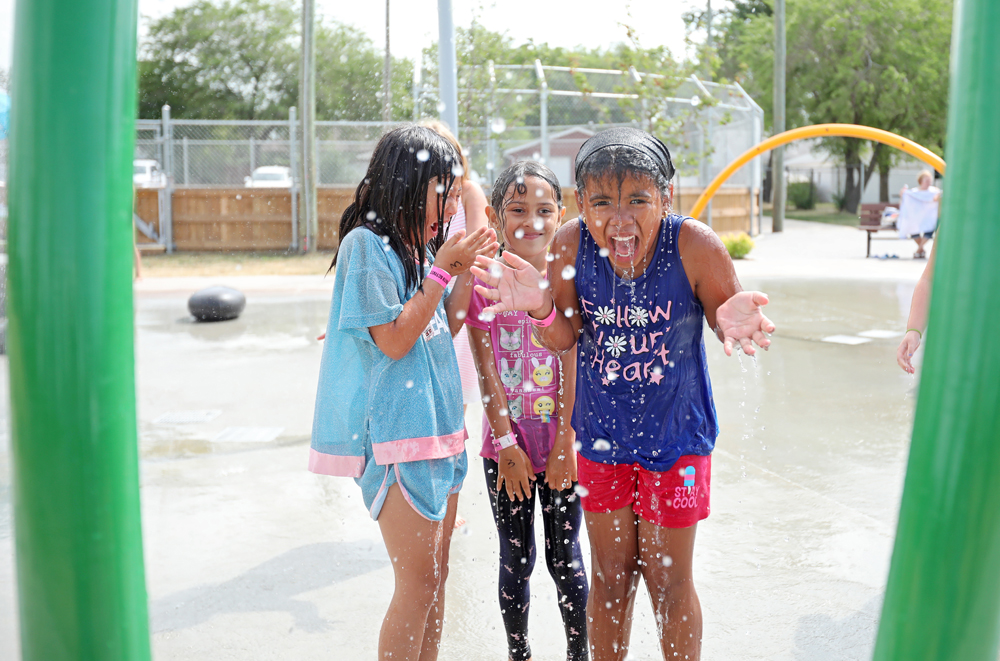 DRENCHED! Eight-year-old Marianella Guerrero reacts after a bucket of water pours over her and friends at the new spray park located at Valleyview Community Centre. (Tim Smith/The Brandon Sun)