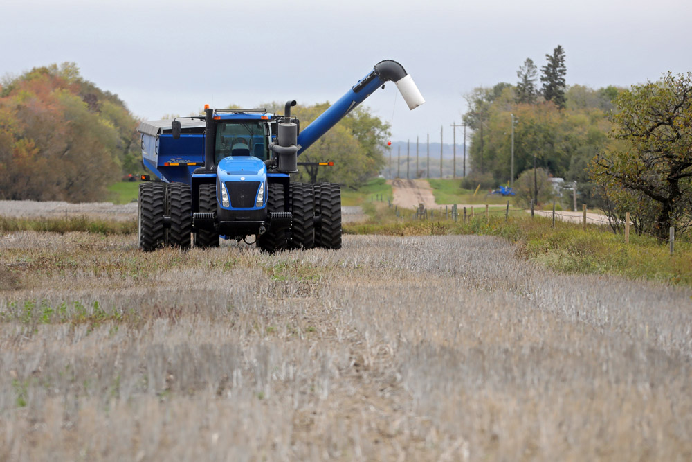 A tractor and grain cart sit idle in a field west of Brandon. (Tim Smith/The Brandon Sun)
