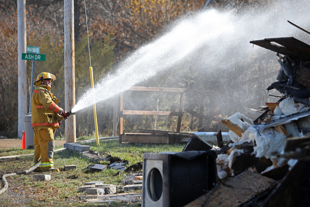 22102019 Oak Lake-Sifton Fire Department members pour water on hot spots in the rubble of a multi family house on Marina Road and Ash Drive in Oak Lake Beach as a back hoe piles the rubble on Tuesday after a fire from Monday thought to have been extinguished flared up again and destroyed the property. The fire also spread to an adjacent trailer. (Tim Smith/The Brandon Sun)