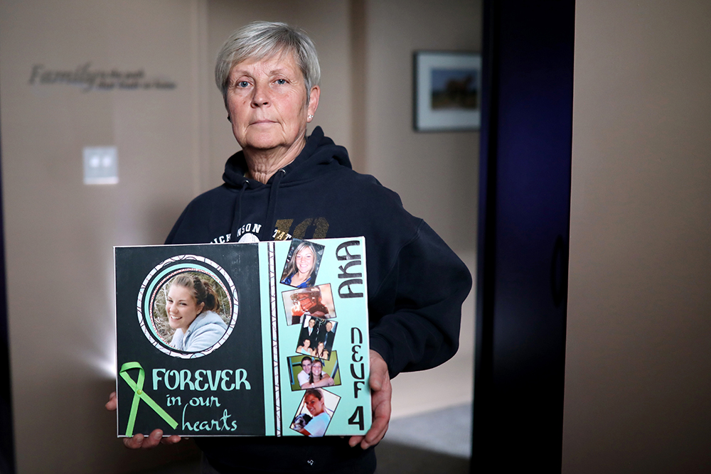 Bev Neufeld holds a collage of photos of her daughter Ashley in her Brandon home on Friday. Ashley, a well-known softball player from Brandon, died in early November 2009 with friends and Dickinson State University Softball teammates Kyrstin Gemar and Afton Williamson when they inadvertently drove into a pond while out stargazing near Dickinson, N.D. (Tim Smith/The Brandon Sun)