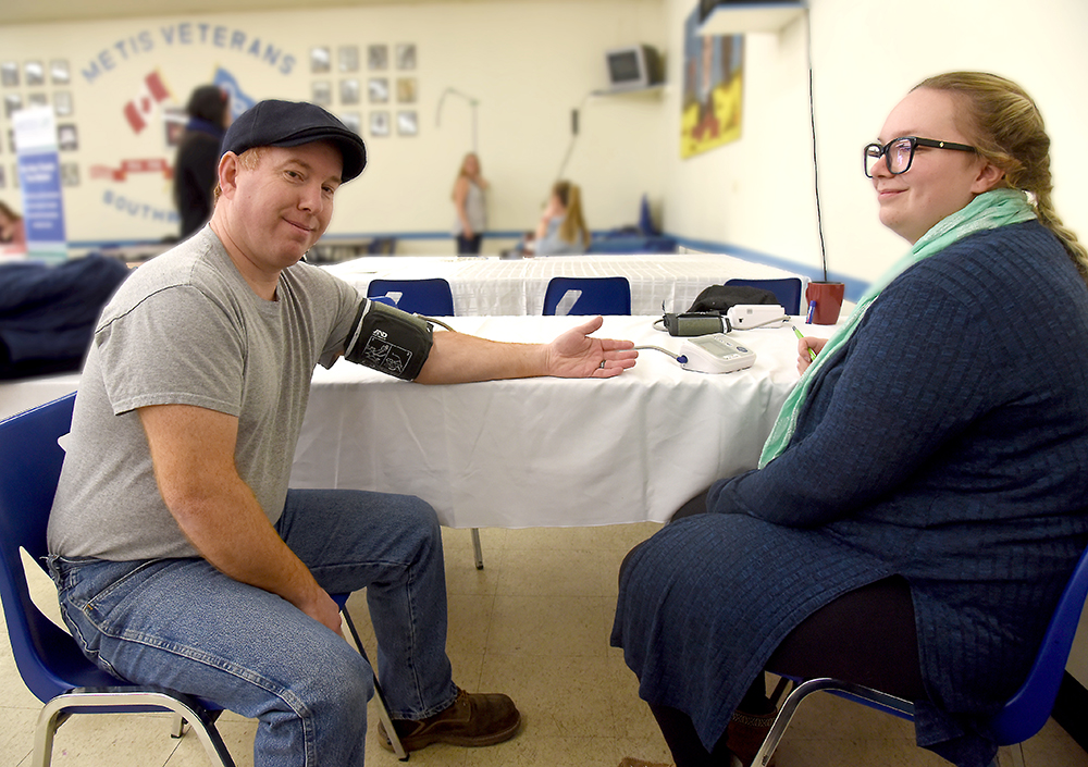 Greg Brown has his blood pressure checked by Sydney Tower during a free clinic Thursday hosted by the Manitoba Metis Federation, Diabetes Canada and Dynacare. (Bud Robertson/The Brandon Sun)