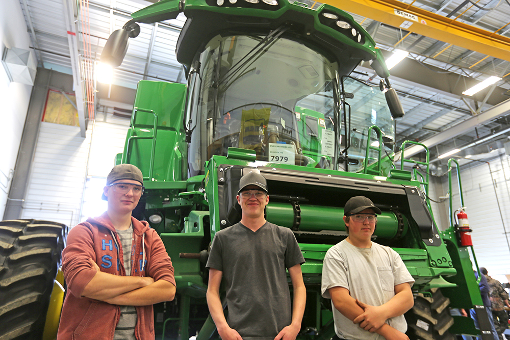 High school students Braeden Smith, Vincent Bauer and Braxton Yurkiwgot have a firsthand look at a John Deere combine at an agricultural equipment boot camp at Assiniboine Community College on Thursday. (Colin Slark/The Brandon Sun)
