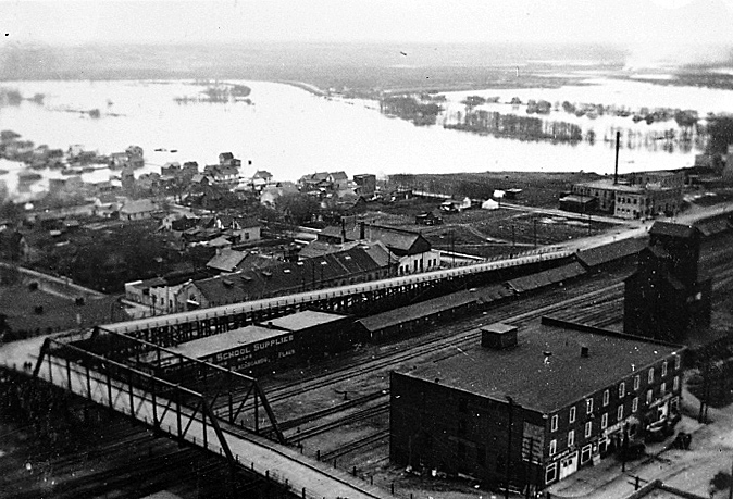This May 1922 photo shows the Assiniboine River in flood, looking south-east at the Eighth Street Bridge. Note the original east ramp to the bridge, as well as Christie School Supplies on the far (south) side of the railway tracks.  (Lawrence Stuckey Collection, S.J. McKee Archives)