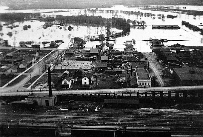 This May 1922 photo shows the original west approach ramp to the Eighth Street Bridge (out of frame, to the right) as well as the Assiniboine River in flood. (Lawrence Stuckey Collection, S.J. McKee Archives)