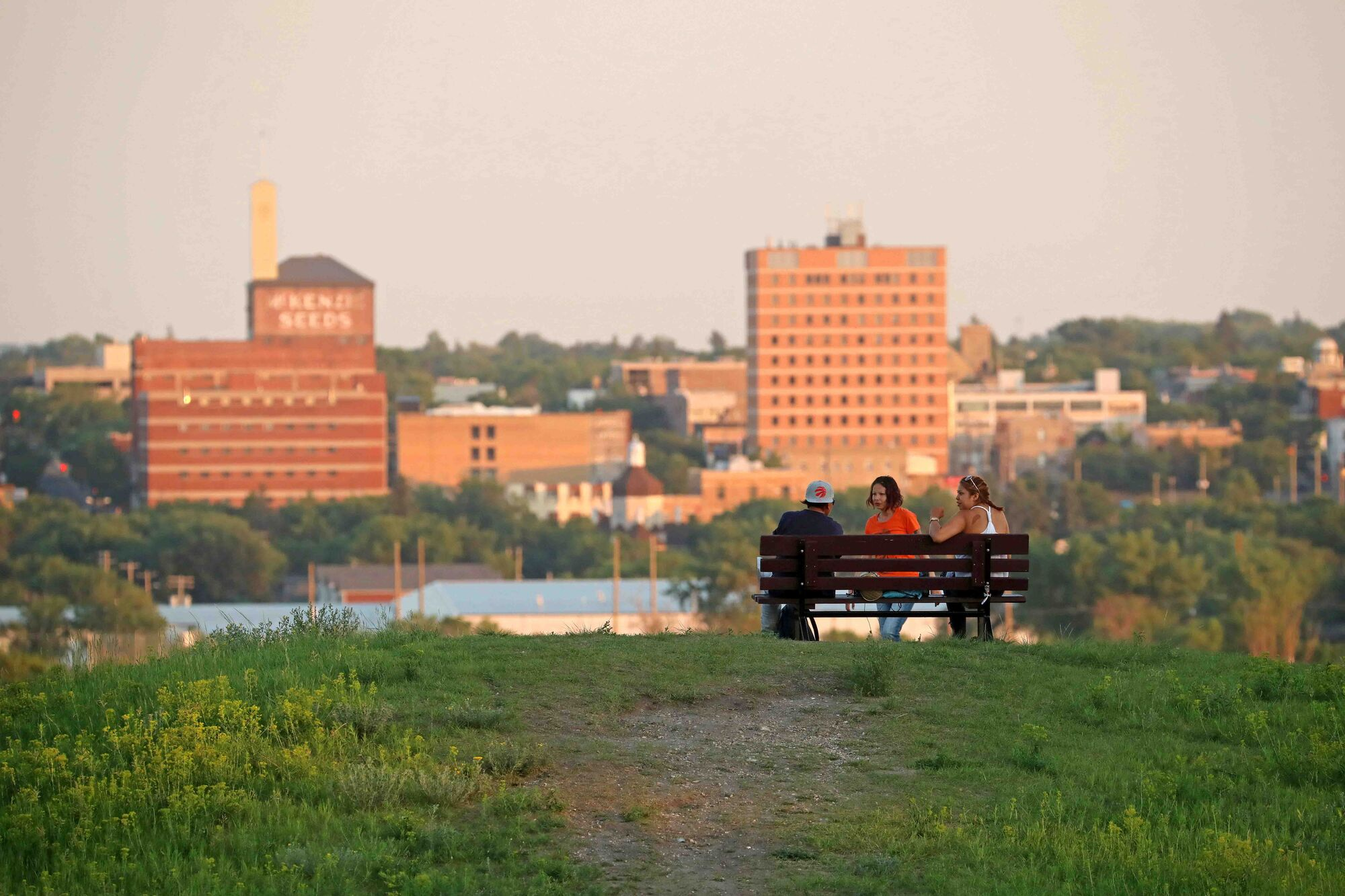 A group look out over the downtown Brandon skyline from Hanbury Hill on a hot summer evening.