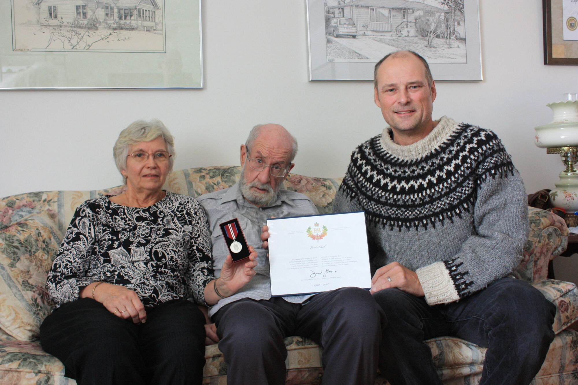 Errol Black (middle) and his wife Margaret Black accept the Queen Elizabeth Diamond Jubilee Medal and certificate from Brandon East MLA Drew Caldwell.