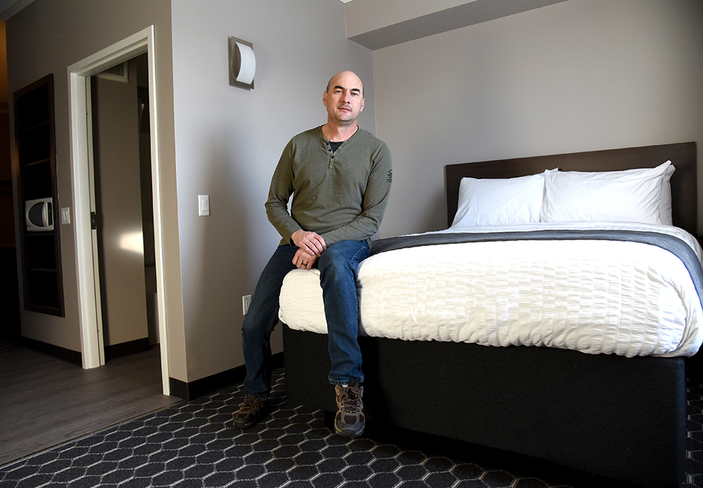 Trevor Rempel, vice-president of sales and marketing with Steel Creek Developers, sits on a bed in the newly opened Blue Crescent Hotel in Rivers. (Bud Robertson/The Brandon Sun)