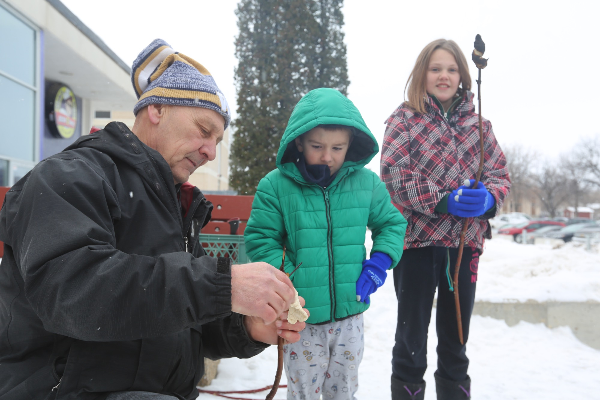 Jim Dyck helps Chase Pople wrap bannock on a stick as Peighton Oickle, bannock already cooked over the fire, looks on.