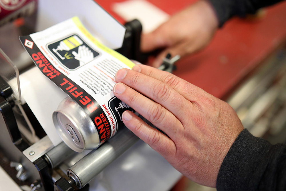 Farmery Estate Brewery co-owner Chris Warwaruk attaches a label to a can of hand sanitizer. (Tim Smith/The Brandon Sun)