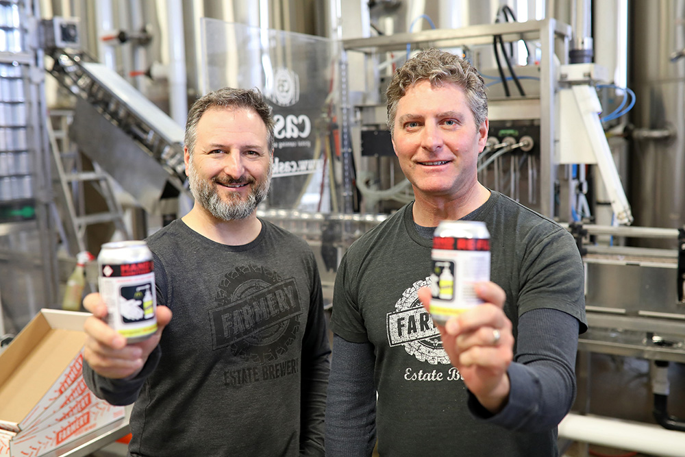 Brothers Chris and Lawrence Warwaruk, owners of Farmery Estate Brewery in Neepawa, show cans of hand sanitizer they've produced as the brewery shifts part of its production from beer to sanitizer to help with measures to stop the spread of the COVID-19 pandemic. (Tim Smith/The Brandon Sun)