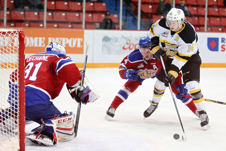 Brandon Wheat Kings forward Ty Lewis (14) readies a shot on netminder Josh Dechaine of the Edmonton Oil Kings while being pursued by Will Warm (4) of the Oil Kings during Western Hockey League action at Westman Place in January 2018.