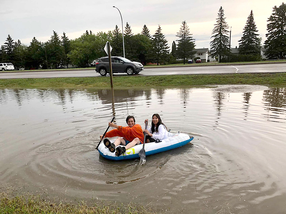 Ten Thorne and Jeremy DIxon go rafting in a roadside ditch in the aftermath of Sunday's storm. (Courtesy Ten Thorne)