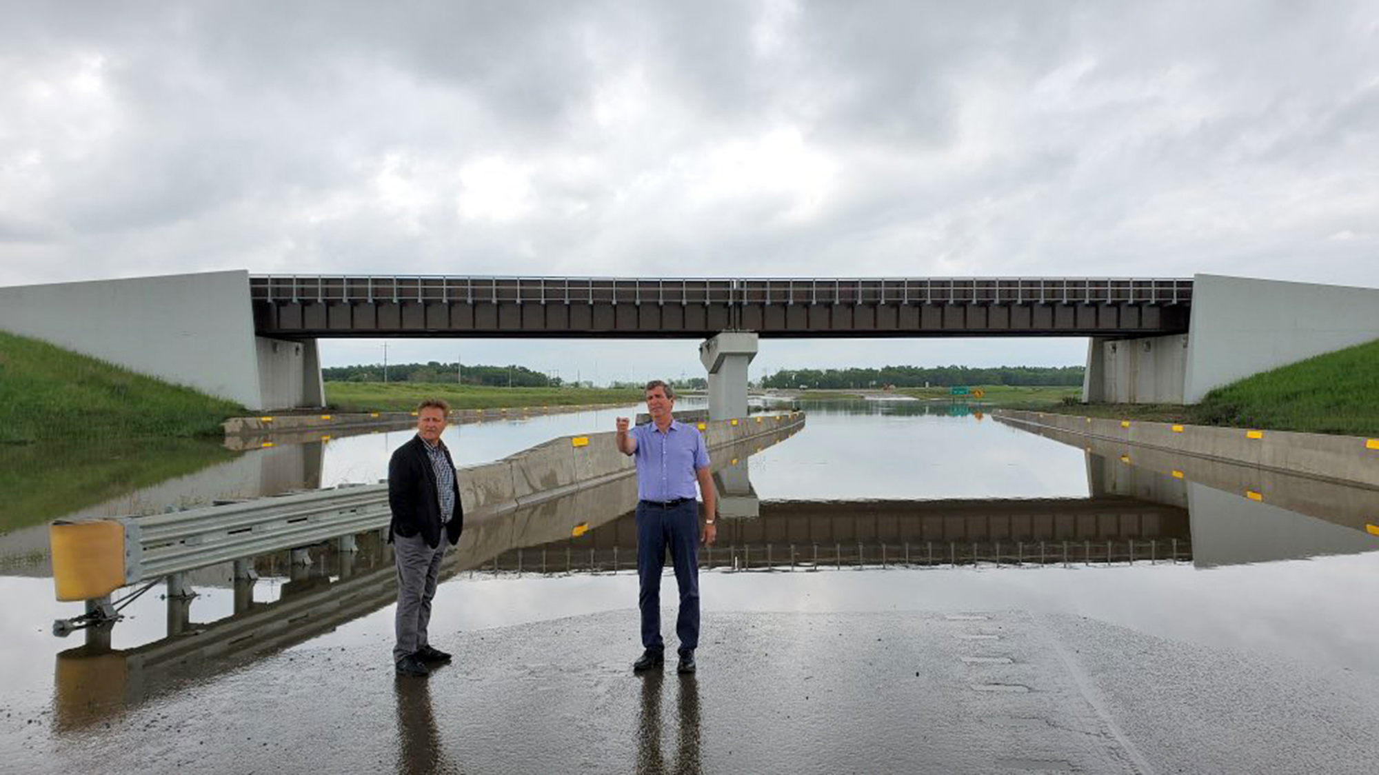 Infrastructure Minister Ron Schuler and Brandon West MLA and Central Services Minister check out a flooded overpass on Highway 110 near the junction with Provincial Road 459 on Tuesday.
