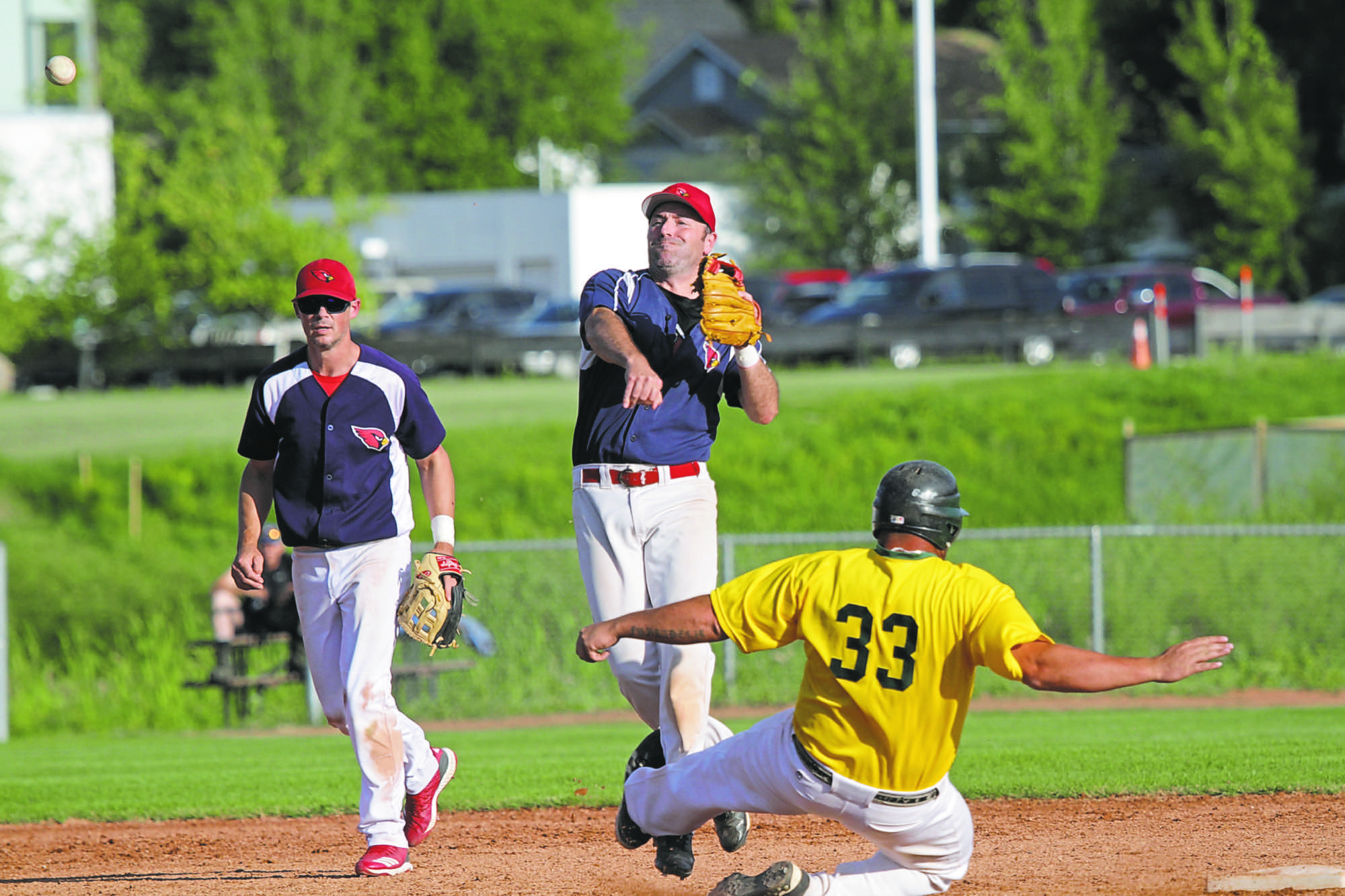 Cardinals Chris Kennedy, centre, attempts to turn a double play as Young Guns Justin Funk slides in the general vicinity of second base while Buddy Mayert looks on during Game 2 of the Andrew Agencies Senior AA Baseball League final at Sumner Field on Thursday. (Thomas Friesen/The Brandon Sun)