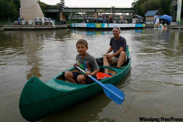Max Oosterhuis, 8, and his father Koert paddle into The Forks to see Fred Penner during last year's River Barge Festival.