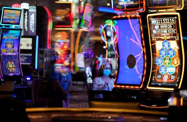 A woman, wearing masks as a precaution against the coronavirus, plays an electronic slot machine during the reopening of the Mirage hotel and casino in Las Vegas, Thursday, Aug. 27, 2020. Great Canadian Gaming Corporation announced today that its casinos in Sydney and Halifax will reopen October 5, 2020. THE CANADIAN PRESS/AP-John Locher